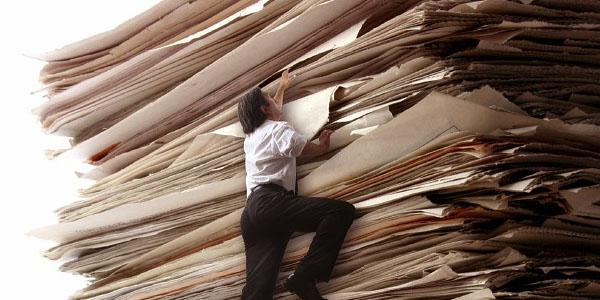 Здесь фото: человек и гора документов
